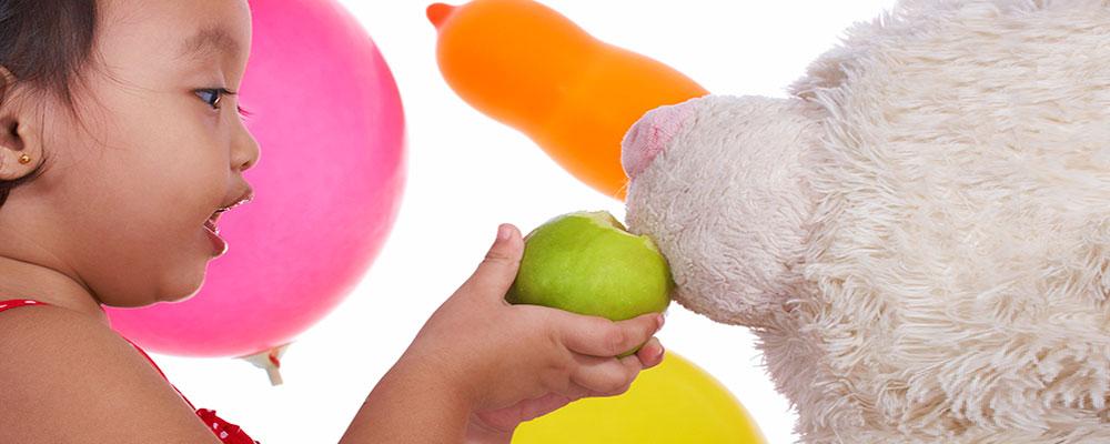 kid-feeding-her-teddy-an-apple-cropped